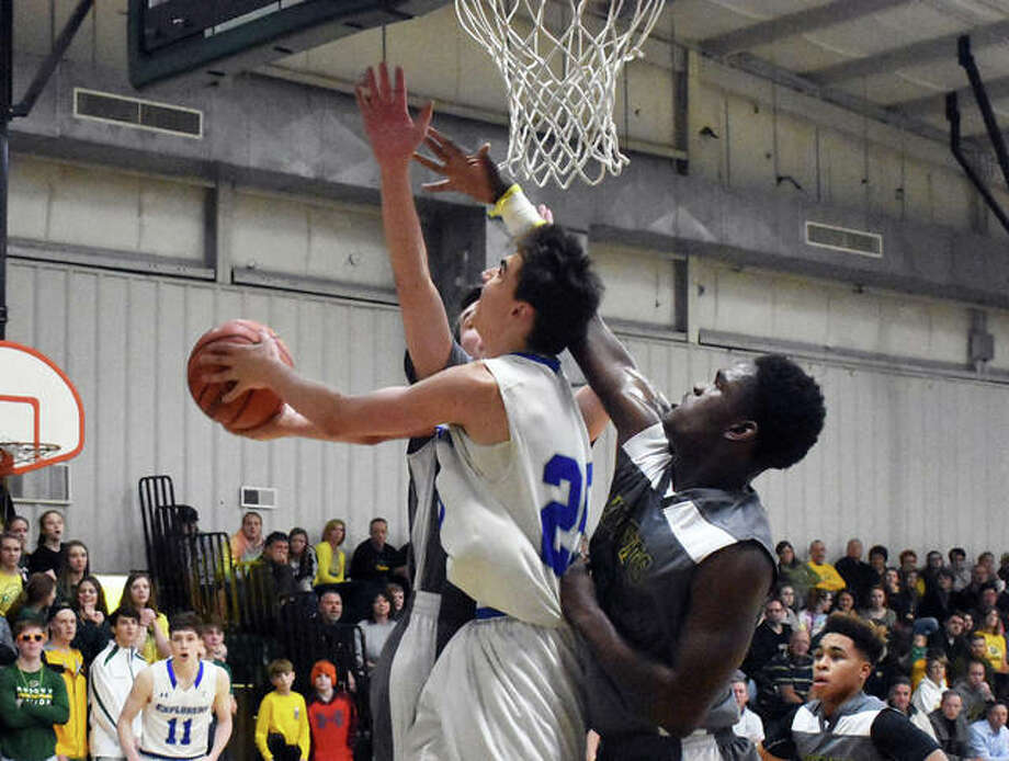 Alton Marquette's Nate Hall, left, goes up for a reverse lay-up with Metro-East Lutheran's DaMonte Bean trying to block it in the second quarter of Saturday's Turkey-Tip Off championship game. Photo: Matt Kamp/Intelligencer