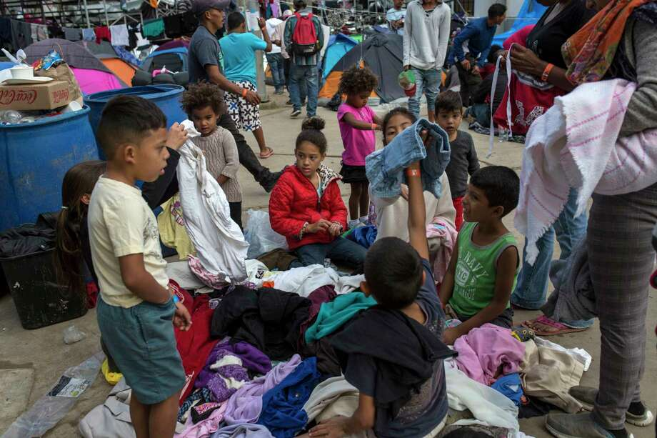 Central American migrant children look through a pile of donated clothes at the Benito Juarez Sports Center serving as a temporary shelter for Central American migrants, in Tijuana, Mexico, Saturday, Nov. 24, 2018. The mayor of Tijuana has declared a humanitarian crisis in his border city and says that he has asked the United Nations for aid to deal with the approximately 5,000 Central American migrants who have arrived in the city. Photo: Rodrigo Abd / Copyright 2018 The Associated Press. All rights reserved.