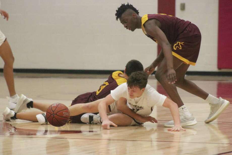 Clear Creek's Jordan Herd's attempt to reach a loose ball is impeded by Jacob Garcia's arm during a second-half loose ball at mid-court. Deer Park's Terry Anderson hovers over the pair. Photo: Robert Avery