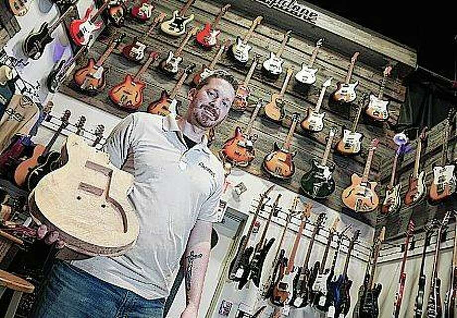 Nate DeMont of DeMont Guitars works on making a guitar out of wood from the 250-year-old Hobson Oak at his shop in Oswego. The oak was cut down in November 2016 in the Chicago suburb of Woodridge. Now it's been auctioned, as a guitar and other art pieces to benefit local charities. Photo: Bev Horne | Daily Herald (AP)