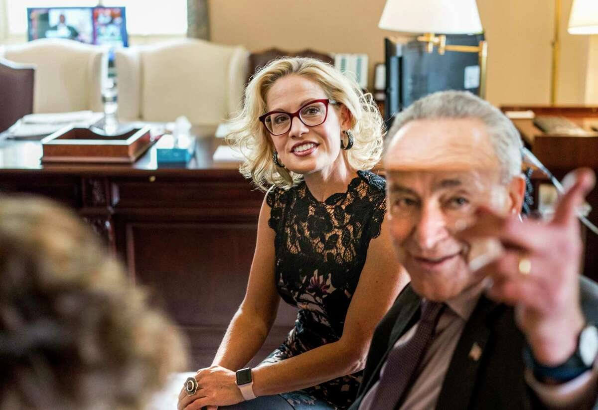 Senator-elect Kyrsten Sinema, D-Ariz., who identifies as bisexual, meets with Senate Minority Leader Chuck Schumer, D-N.Y., in his office on Capitol Hill on Nov. 13.