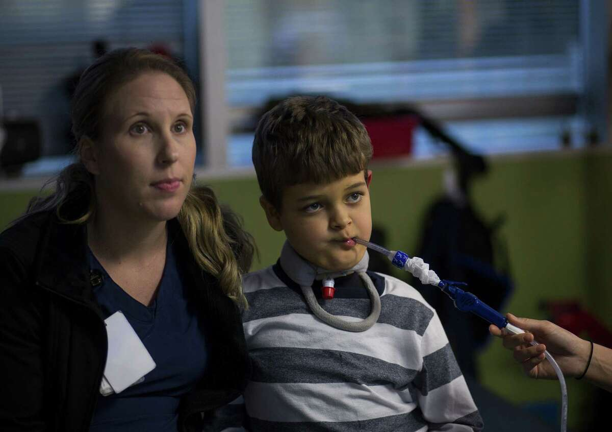 Seven-year-old Braden Scott sets up a Wii to play a game with occupational therapist Jamie Beckham during a physical therapy session at TIRR Memorial Hermann in The Woodlands, Monday, Nov. 12, 2018. Two-years ago Braden was diagnosed with acute flaccid myelitis, or AFM. The polio-like illness has affected Braden's nervous system, causing muscle problems including having trouble swallowing, requiring Braden to sometimes need suction.