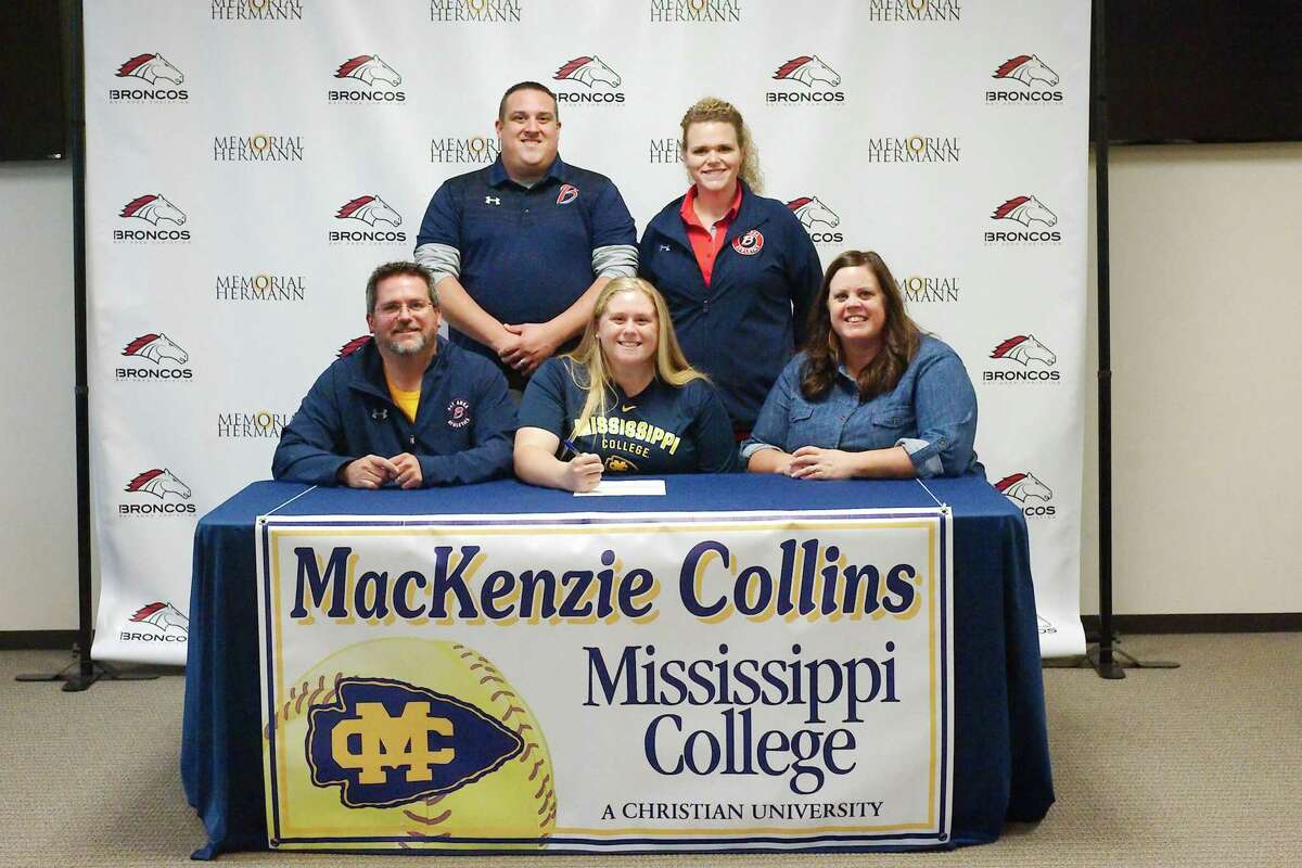 Bay Area Christian Athletic Director Kyle Kennedy and softball coach Meagan Callaway stand with student Mackenzie Collins who sits with her father, Curtis, and her mother, Kelly, as Mackenzie prepares to sign a letter of intent to play softball at Mississippi College.