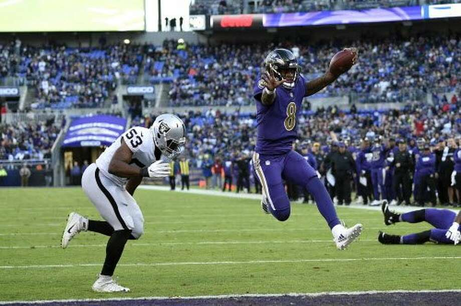 Baltimore Ravens quarterback Lamar Jackson (8) scores a touchdown in front of Oakland Raiders linebacker Jason Cabinda in the second half of an NFL football game, Sunday, Nov. 25, 2018, in Baltimore. (AP Photo/Nick Wass) Photo: Nick Wass / Associated Press