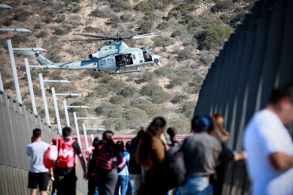 A United States Military helicopter flies past a pedestrian bridge after the closing of the United States-Mexico border was ordered on November 25, 2018 at the San Ysidro border crossing point south of San Diego, California. - US officials closed a border crossing in southern California on Sunday after hundreds of migrants tried to breach a border fence from the Mexican city of Tijuana, US authorities announced. The US Customs and Border Protection office in San Diego, California, said on Twitter that it had closed both north and south access to vehicle traffic at the San Ysidro border post, before also suspending pedestrian crossings. (Photo by Sandy Huffaker / AFP)SANDY HUFFAKER/AFP/Getty Images