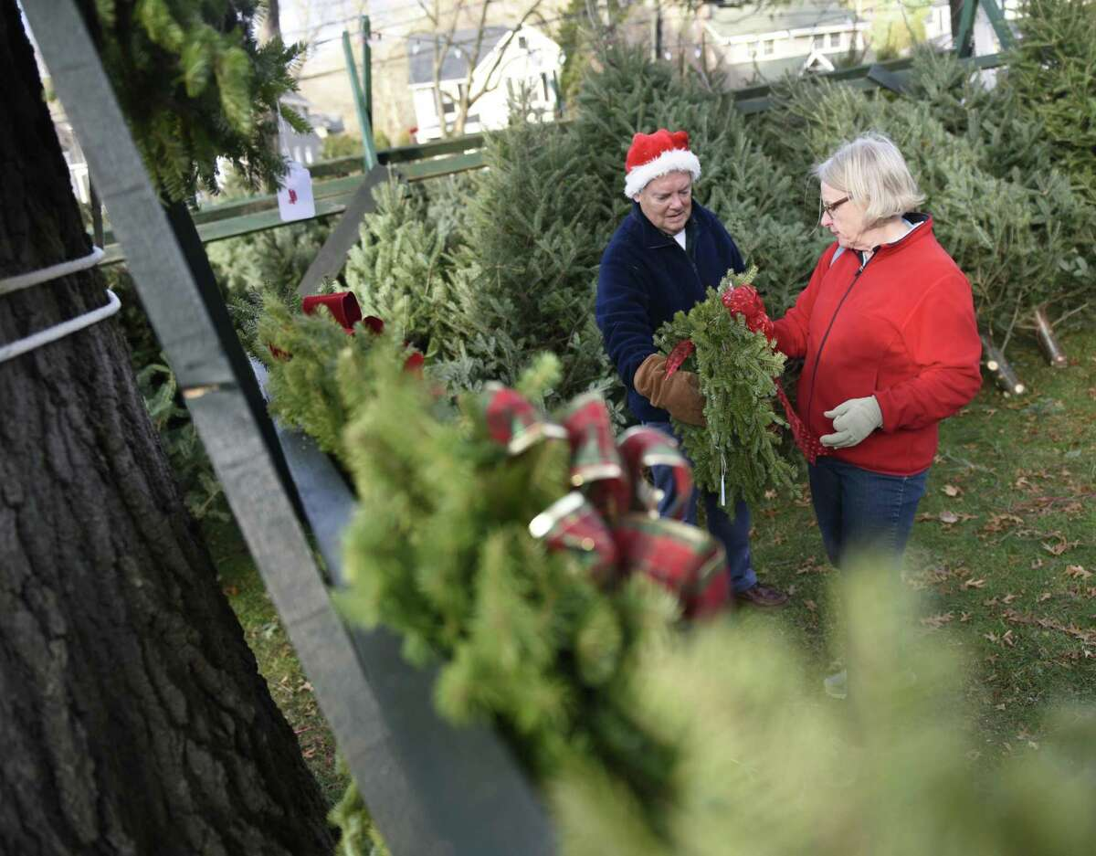Church volunteers Anders and Mariann Ekernas select a wreath at the annual Christmas Tree & Wreath Sale at First Congregational Church of Old Greenwich in Old Greenwich, Conn. Sunday, Nov. 25, 2018. FCCOG is selling 450 top grade New Hampshire trees and 200 wreaths with all benefits going to charities Kids in Crisis, SoundWaters, Pacific House, Building 1 Community, BackCountry Jazz, and The Den for Grieving Kids.