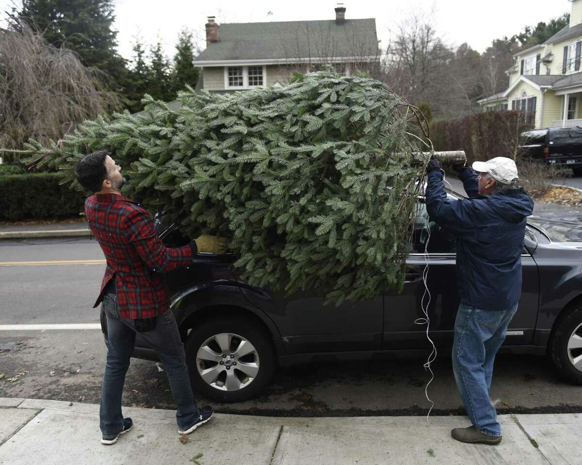 Associate Pastor the Rev. Patrick Collins, left, and church volunteer Gary Miller tie a tree down to a car at the annual Christmas Tree & Wreath Sale at First Congregational Church of Old Greenwich in Old Greenwich, Conn. Sunday, Nov. 25, 2018. FCCOG is selling 450 top grade New Hampshire trees and 200 wreaths with all benefits going to charities Kids in Crisis, SoundWaters, Pacific House, Building 1 Community, BackCountry Jazz, and The Den for Grieving Kids.