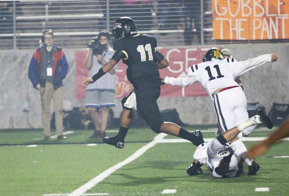 Liberty's Gio Lopez grabs the jersey of Giddings quarterback Alex Delatorre to slow him down and prevent a big run in the Panthers loss to the Buffaloes, 21-13. Photo: David Taylor / HCN