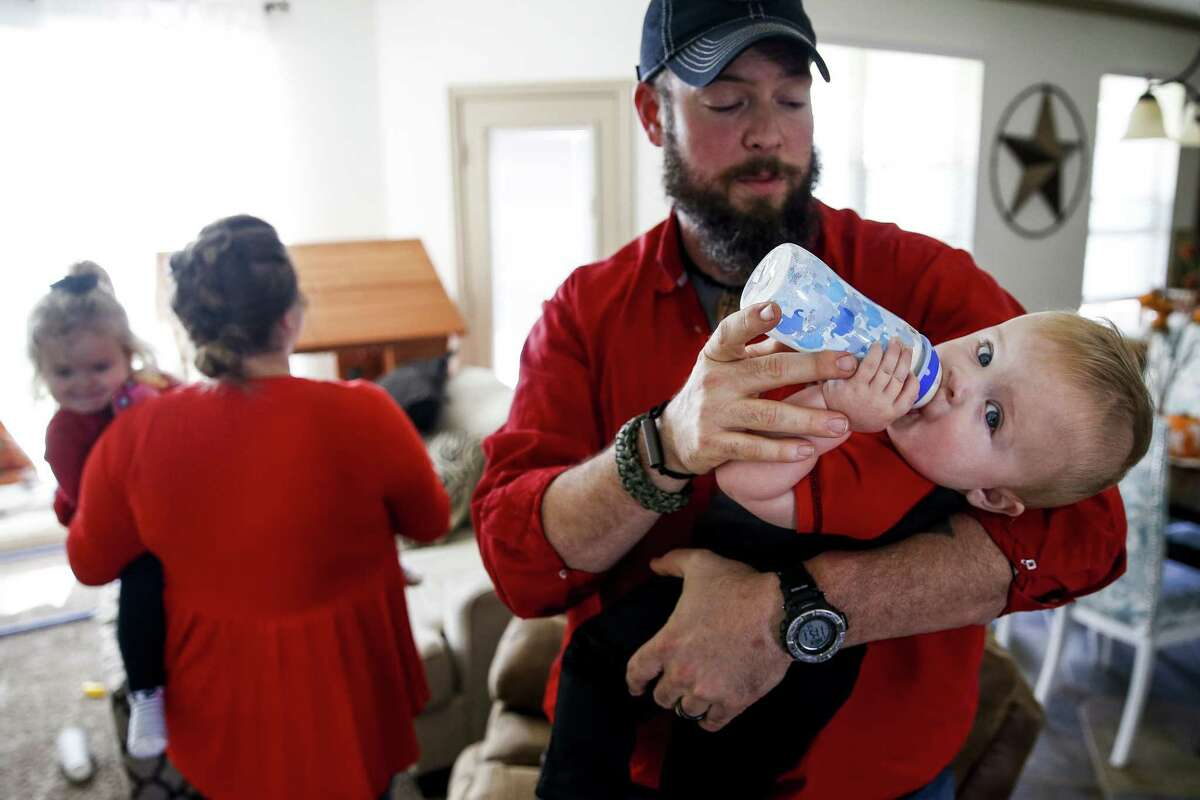 Dillon Bright feeds his nine-month-old son, Mason Bright, a bottle as Melissa Bright holds her daughter, Charlotte Bright, 2, in the background Saturday, Nov. 3, 2018, in Tomball. Child Protective Services is facing sanctions after improperly removing the Bright's children from their home after Mason fell and fractured his skull when he was five months old.