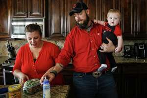 Melissa Bright prepares lunch for her daughter as Dillon Bright feeds his nine-month-old son, Mason Bright, a bottle on Nov. 3, 2018, in Tomball. Child Protective Services was hit with $127,000 in sanctions after improperly removing the Bright's children from their home after Mason fell and fractured his skull when he was five months old.
