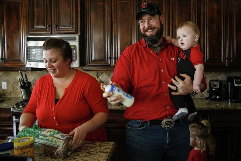 Melissa Bright prepares lunch for her daughter as Dillon Bright feeds his nine-month-old son, Mason Bright, a bottle Saturday, Nov. 3, 2018, in Tomball. Child Protective Services is facing sanctions after improperly removing the Bright's children from their home after Mason fell and fractured his skull when he was five months old. Photo: Michael Ciaglo, Houston Chronicle / Staff Photographer / Michael Ciaglo