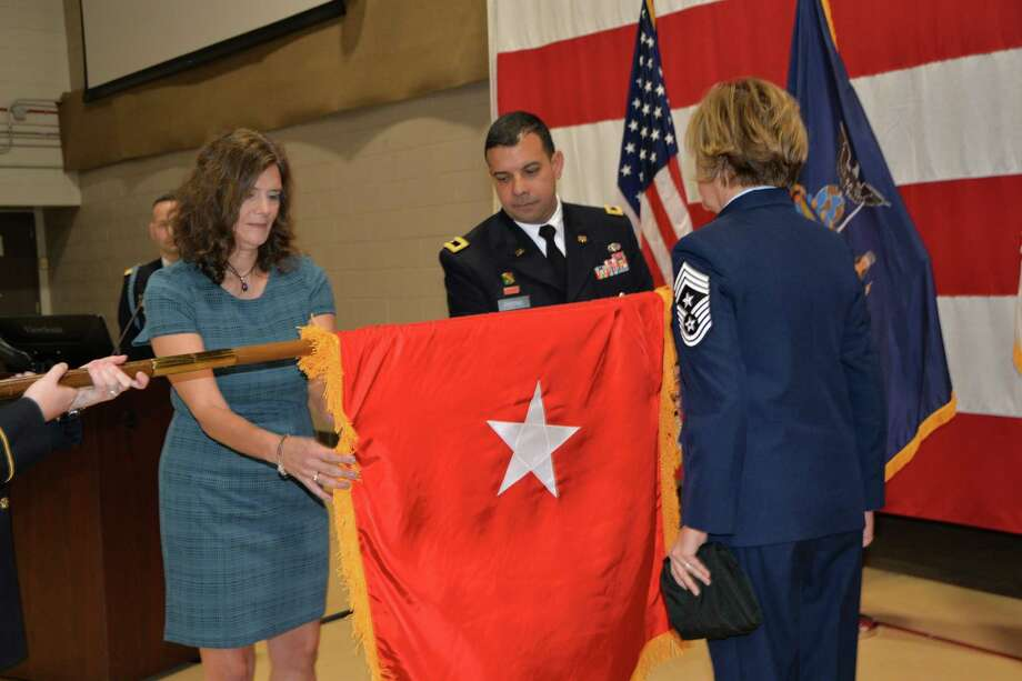 Newly promoted New York Army National Guard Brig. Gen. John Andonie and his wife, Kathleen, left, join Air Force Chief Master Sgt. Amy Giaquinto, the senior enlisted leader of the New York National Guard, in unfurling Andonie?s general officer?s flag in Latham. (Capt. Jean Marie Kratzer / New York Army National Guard)
