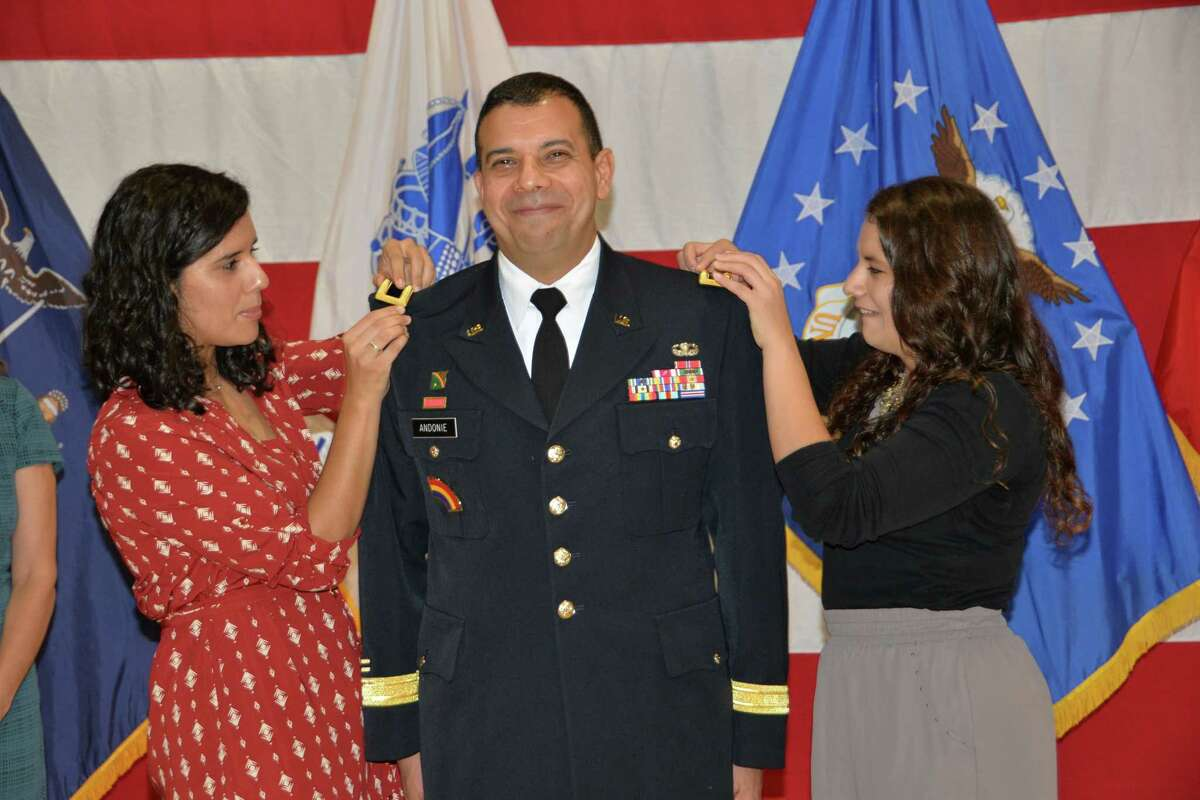 New York Army National Guard Brig. Gen. John Adonie?s receives the brigadier general shoulder straps bearing his new one-star general rank from his daughters Rachel, left, and Elizabeth, during his promotion ceremony in Latham. (Capt. Jean Marie Kratzer / New York Army National Guard)