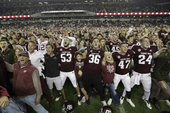 Texas A&M players and fans whoop it up after the Aggies' 74-72, seven-overtime victory over LSU at Kyle Field on Saturday night.