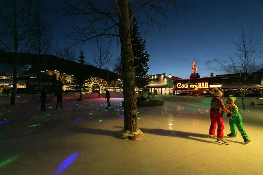 Skaters in Jackson, Wyo., take to an outdoor ice rink, bathed in the neon glow of the Million Dollar Cowboy Bar. Photo: Jackson Hole Mountain Resort, HO / TNS / Chicago Tribune