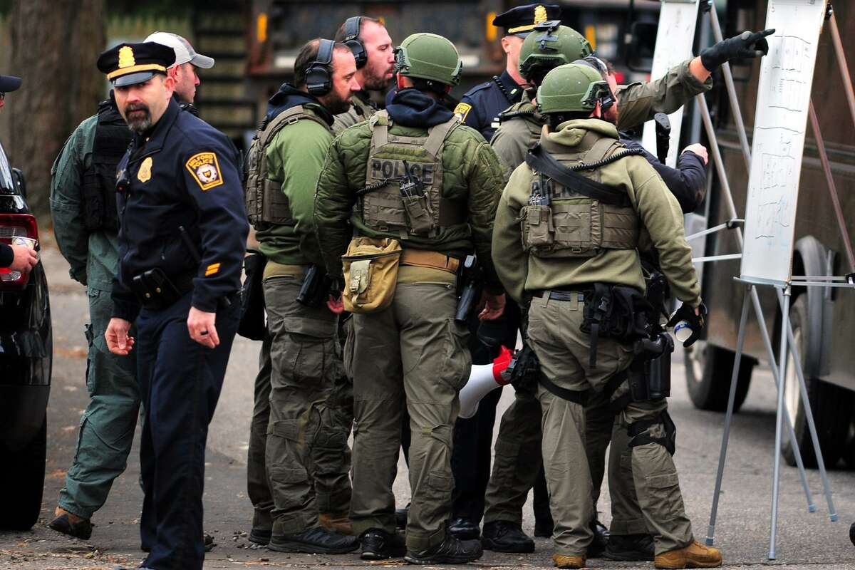 Police officers at the scene of a standoff Monday morning on Falmouth Street in Milford.