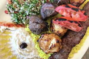 Mixed grill plate with cubes of lamb, chicken and a kebab made from a blend of beef and lamb with sides of tabbouleh and baba ghanoush at Babil Cafe.