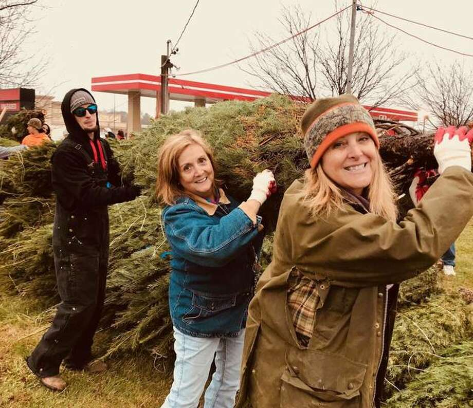 Circuit Judge Kyle Napp, in front, and Ruth Reeves, a therapist with Chestnut Health Systems, help unload a truckload of trees for the Lyons Christmas Tree lot in Edwardsville. The Madison County Drug Court staff helped with the project as a community service. Behind Reeves is one of the drug court defendants.