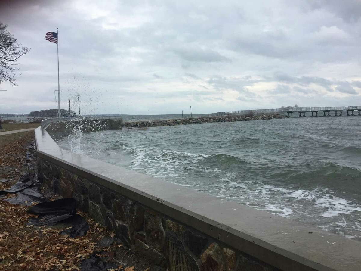 Waves from a high tide crash ashore at Calf Pasture Beach in Norwalk on Monday, Nov. 26, 2018. Water from a high tide covers the road near Calf Pasture Beach in Norwalk on Monday, Nov. 26, 2018. The National Weather Service has posted a Coastal Flood Warning for southern Fairfield and New Haven counties from noon to 3 p.m. Monday and from midnight to 4 a.m. Tuesday.