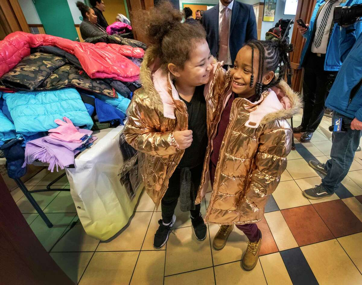 Best friends and class mates Tionna Vaughan, 8, left and Jaliah Haynes, 8, show off their new coats at the Schuyler Achievement Academy after they choose a new coat, gloves and a hat donated as part of the Cash for Coats Drive put on by local businesses and private donation Monday Nov. 26, 2018 in Albany, N.Y. (Skip Dickstein/Times Union)