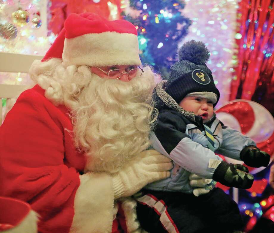 Kole Funk, 18 months, of Clarkston, was not sure of what to make of his encounter with Santa Claus, Friday night, at the Pigeon Town Lighting. Photo: Paul P. Adams/Huron Daily Tribune