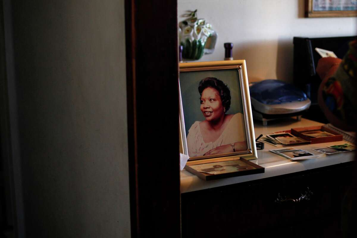 In this Tuesday, March 12, 2013 photo, Brenda Gordon looks at photos of her mother, Carol Alford, at her apartment in Los Angeles. Alford was allegedly murdered by Samuel Little in 1987.