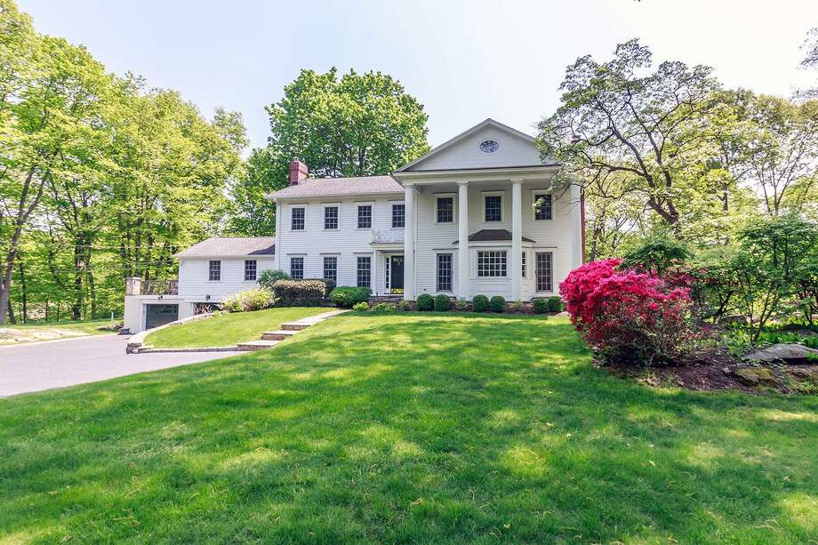 The stately colonial house at 46 Delafield Island Road is perched atop an attractive knoll in the private Delafield Island Association.
