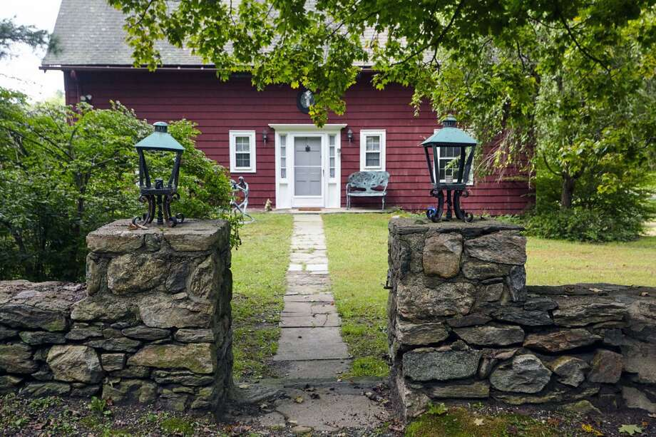 The barn-style colonial house with a gambrel roof at 69 Kellogg Hill Road sits on a three-acre level and gently sloping corner lot in lower Weston.
