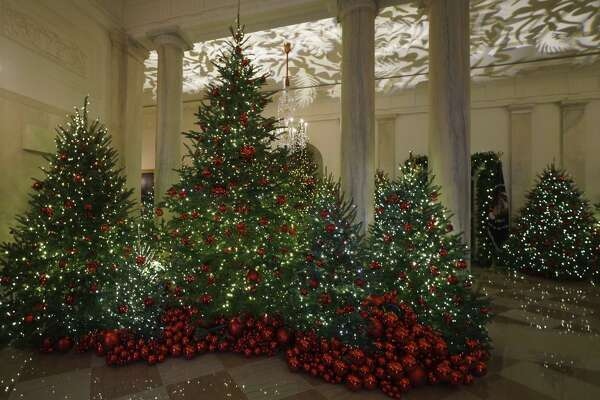 """Grand Foyer and Cross Hall are seen during the 2018 Christmas preview at the White House in Washington, Monday, Nov. 26, 2018. Christmas has arrived at the White House for 2018 as first lady Melania Trump unveiled the holiday decor. She designed the decor, which features a theme of """"American Treasures."""" (AP Photo/Carolyn Kaster)"""