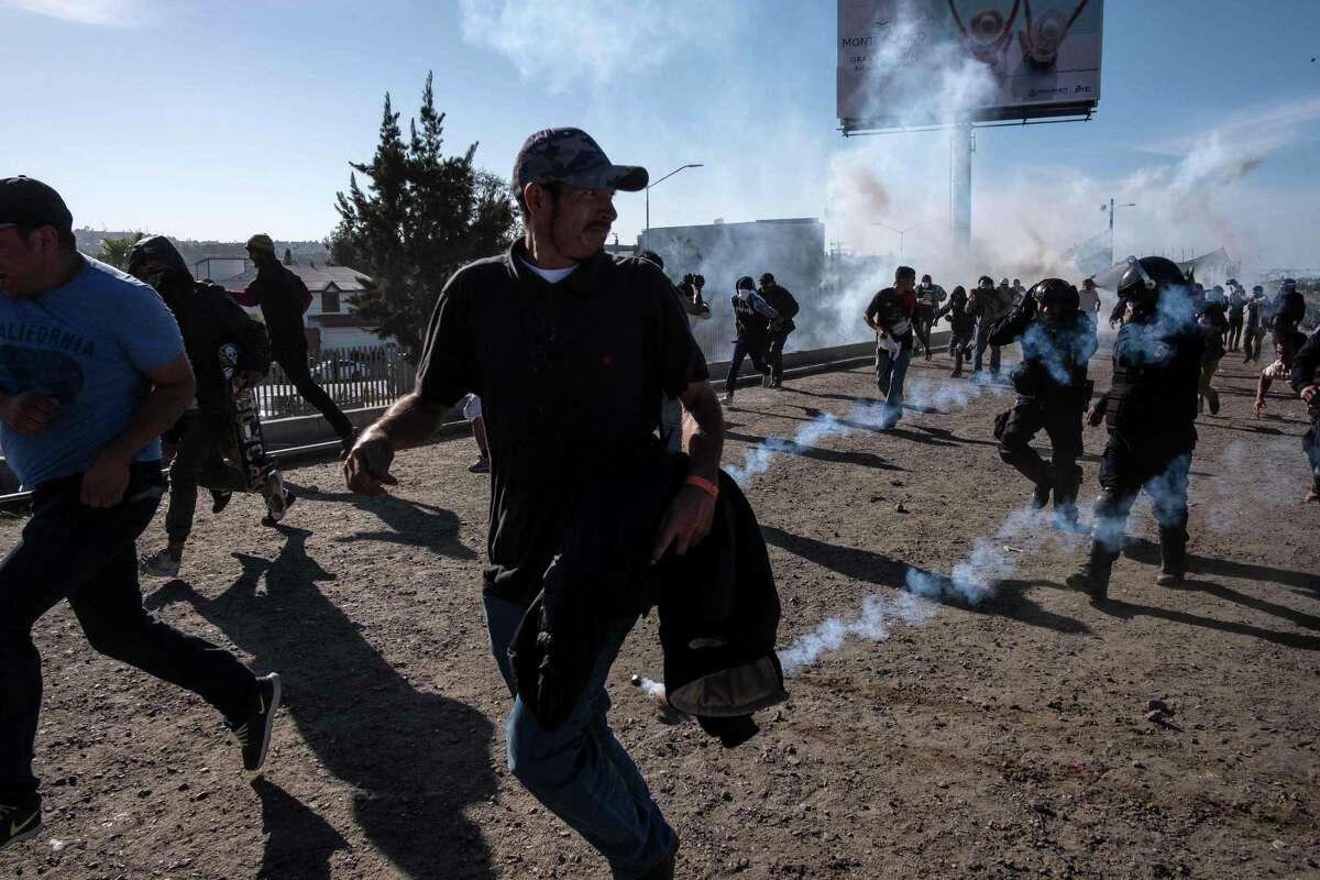 TOPSHOT - Central American migrants -mostly Hondurans- run along the Tijuana River near the El Chaparral border crossing in Tijuana, Baja California State, Mexico, near US-Mexico border, after the US border patrol threw tear gas from the distance to disperse them after an alleged verbal dispute, on November 25, 2018. - US officials closed the San Ysidro crossing point in southern California on Sunday after hundreds of migrants, part of the