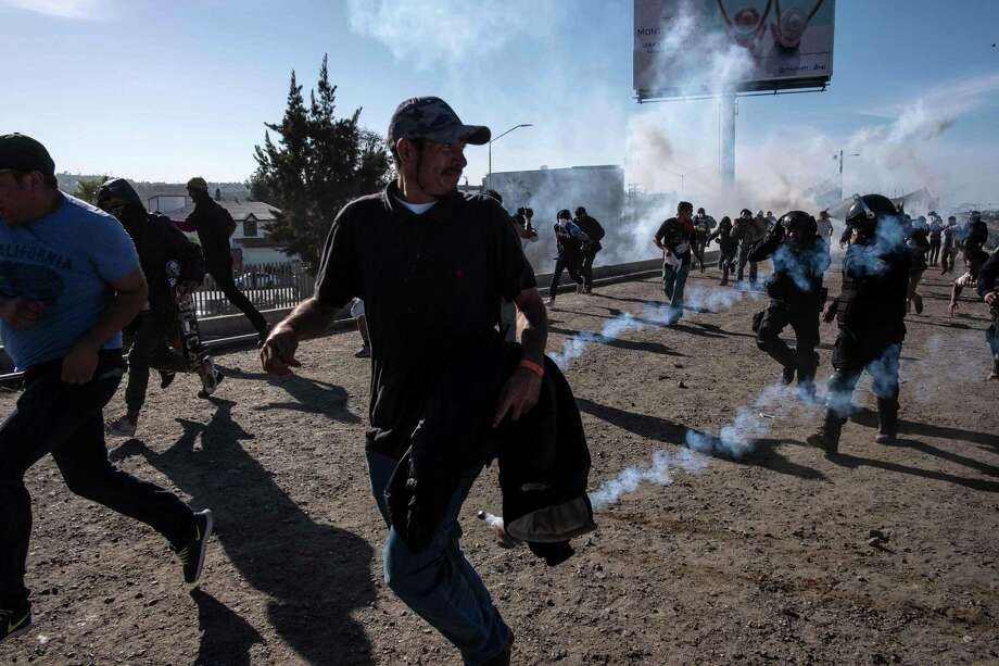 "TOPSHOT - Central American migrants -mostly Hondurans- run along the Tijuana River near the El Chaparral border crossing in Tijuana, Baja California State, Mexico, near US-Mexico border, after the US border patrol threw tear gas from the distance to disperse them after an alleged verbal dispute, on November 25, 2018. - US officials closed the San Ysidro crossing point in southern California on Sunday after hundreds of migrants, part of the ""caravan"" condemned by President Donald Trump, tried to breach a fence from Tijuana, authorities announced. (Photo by GUILLERMO ARIAS / AFP)GUILLERMO ARIAS/AFP/Getty Images Photo: GUILLERMO ARIAS, Contributor / AFP/Getty Images / AFP or licensors"