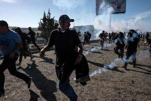 """TOPSHOT - Central American migrants -mostly Hondurans- run along the Tijuana River near the El Chaparral border crossing in Tijuana, Baja California State, Mexico, near US-Mexico border, after the US border patrol threw tear gas from the distance to disperse them after an alleged verbal dispute, on November 25, 2018. - US officials closed the San Ysidro crossing point in southern California on Sunday after hundreds of migrants, part of the """"caravan"""" condemned by President Donald Trump, tried to breach a fence from Tijuana, authorities announced. (Photo by GUILLERMO ARIAS / AFP)GUILLERMO ARIAS/AFP/Getty Images"""