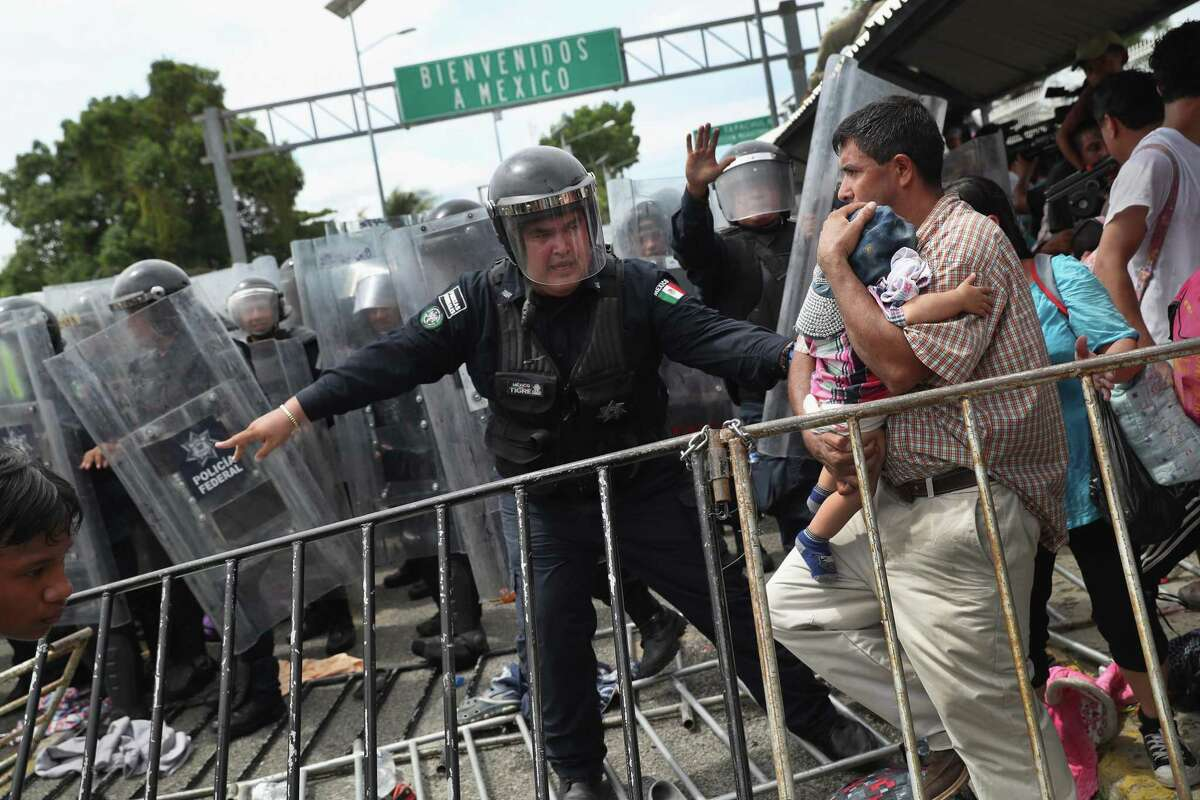 *2018 Year In Focus - News* CIUDAD TECUN UMAN, GUATEMALA - OCTOBER 19: A Mexican riot policeman protects an immigrant father and child during a clash between police and the migrant caravan on the border between Mexico and Guatemala on October 19, 2018 in Ciudad Tecun Uman, Guatemala. A faceoff occurred when the caravan of thousands of migrants tried to enter Mexico after pushing past Guatemalan security forces. The caravan pried open the gate into Mexico but were pushed back by Mexican riot police. Some immigrants threw stones at police who then fired tear gas into the crowd. (Photo by John Moore/Getty Images)