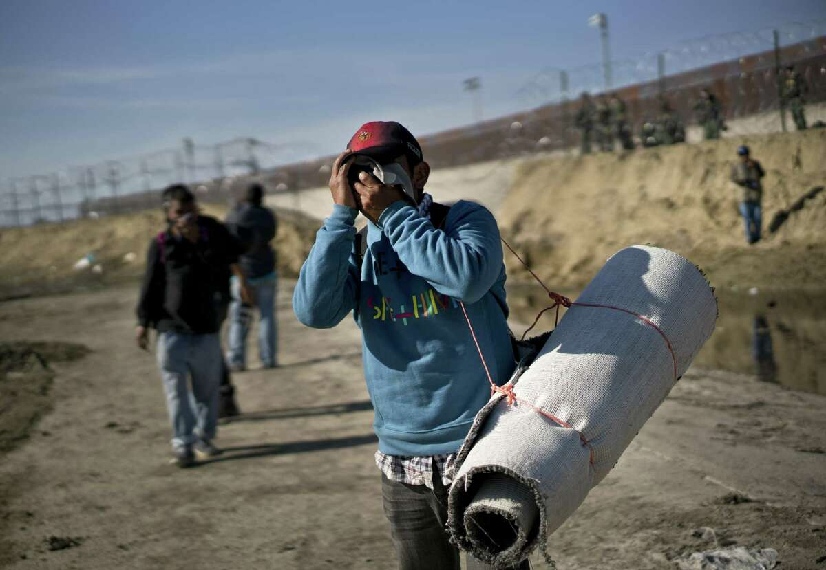 A migrant carrying a roll of carpet wipes his face after U.S. border agents fired tear gas at a group of migrants who had pushed past Mexican police at the Chaparral border crossing in Tijuana, Mexico, Sunday, Nov. 25, 2018. The mayor of Tijuana has declared a humanitarian crisis in his border city and says that he has asked the United Nations for aid to deal with the approximately 5,000 Central American migrants who have arrived in the city. (AP Photo/Ramon Espinosa)