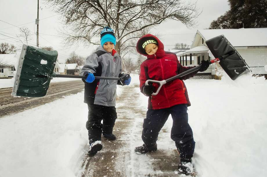 "Dylon Anderson, 11, left, and Noah Anderson, 10, right, work to shovel the driveway of their home on Monday, Nov. 26, 2018 in Midland. ""It's better than being stuck inside,"" Noah said. It was the third time the boys shoveled on Monday as snowfall continued in Midland. (Katy Kildee/kkildee@mdn.net) Photo: (Katy Kildee/kkildee@mdn.net)"