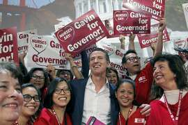 FILE -- In this Dec. 2, 2015 file photo Lt. Gov. Gavin Newsom, the Democratic candidate for governor, meets with more than 1,000 registered nurses from California and cross the nation in Los Angeles. Newsom backed a California Nurses Association proposal to eliminate insurance companies and give everyone state -funded health coverage. Newsom's opponent, Republican John Cox opposes a government-run health care system. (AP Photo/Nick Ut, File)