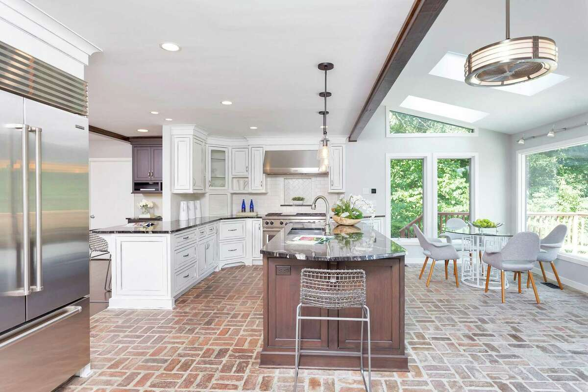 The updated eat-in chef's kitchen at 20 Hunt Lane in Weston features granite counters, high-end appliances including a Wolf range, skylights and a sunny breakfast area overlooking the deck. The contemporary is on 2.8 acres overlooking the Aspetuck River.