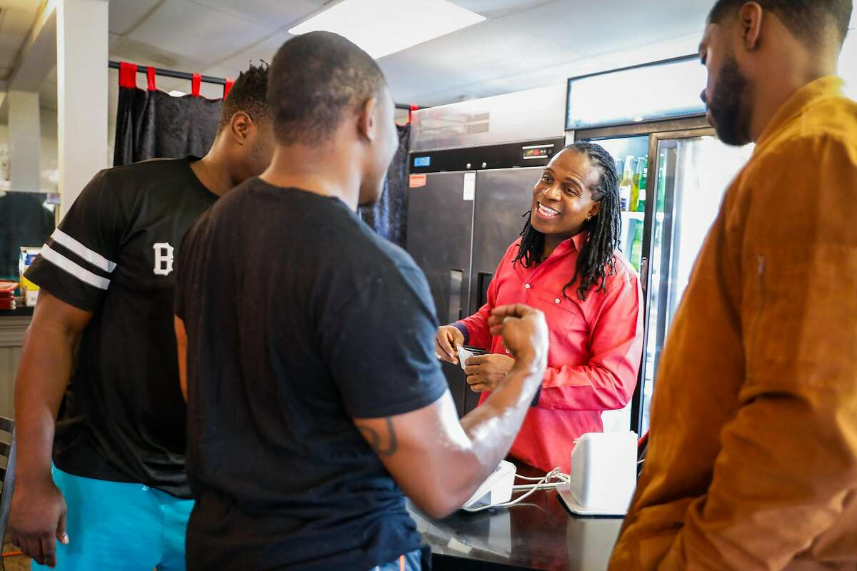Owner Dougie Uso (center) chats with a takeout customers at Kendejah, the Bay Area's only Liberian restaurant in San Leandro, California, on Sunday, Nov. 25, 2018.