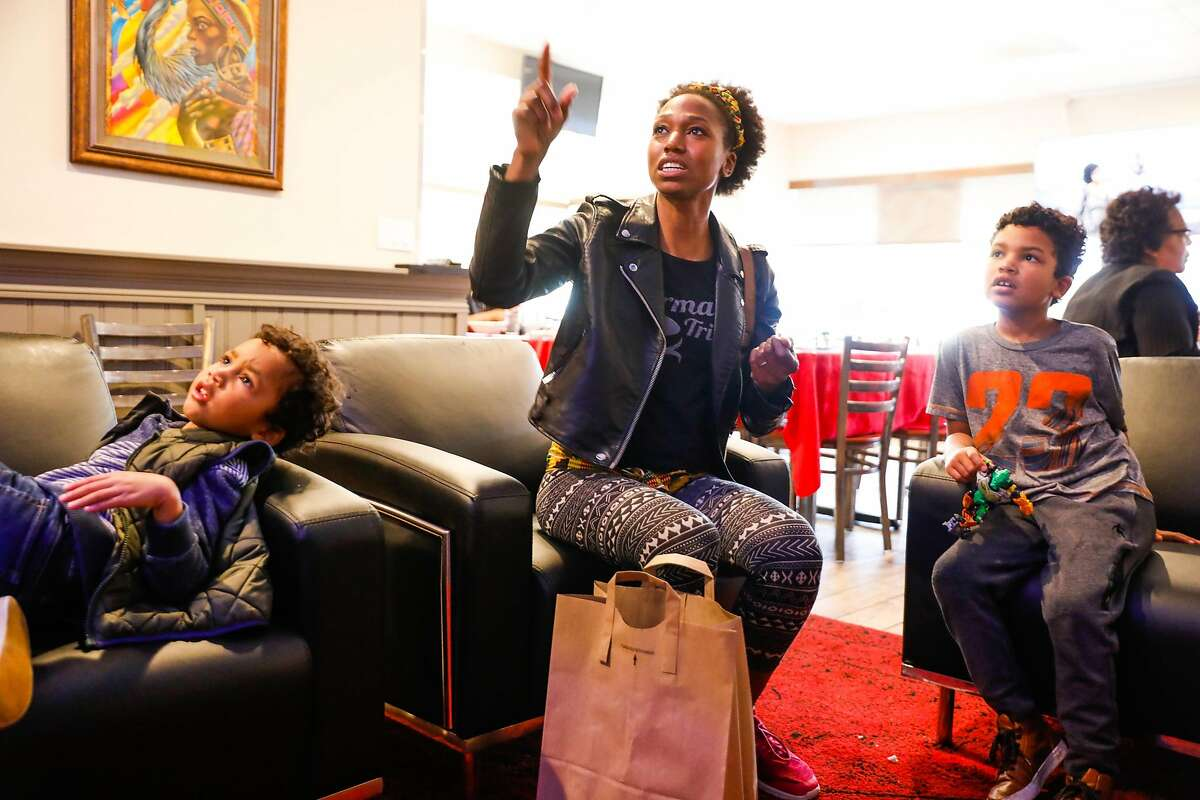 Alicia Langlais (center) watches television with her kids Solomon, 6 (right) and Malakai, 4 after grabbing food to-go at Kendejah, the Bay Area's only Liberian restaurant in San Leandro, California, on Sunday, Nov. 25, 2018.