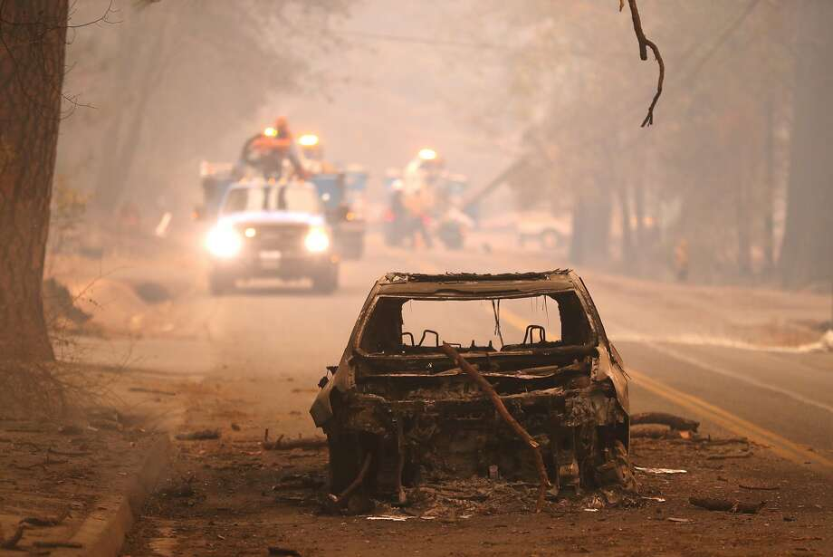 As PG&E crews work behind it, a burned out car sits in Bille Road after Camp Fire in Paradise, Calif. on Friday, November 9, 2018. Photo: Scott Strazzante / The Chronicle