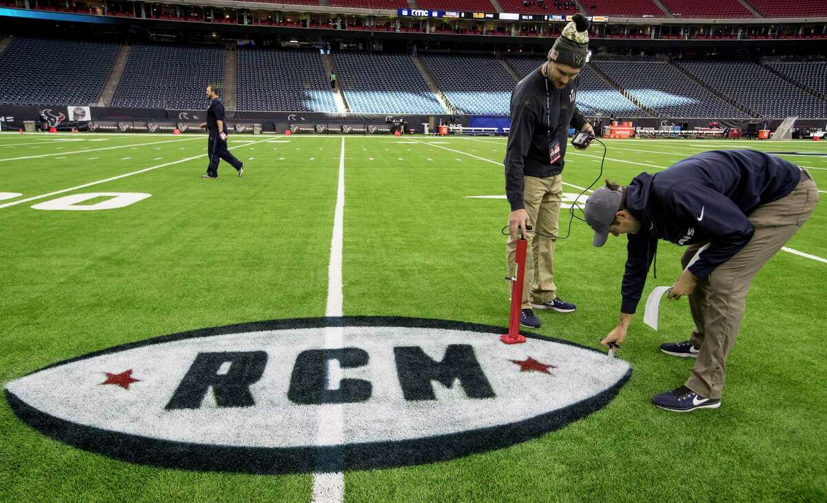 The NRG Stadium grounds crew tests the turf, over a logo honoring Texans founder Robert C. McNair, before an NFL football game against the Tennessee Titans at NRG Stadium on Monday, Nov. 26, 2018, in Houston.