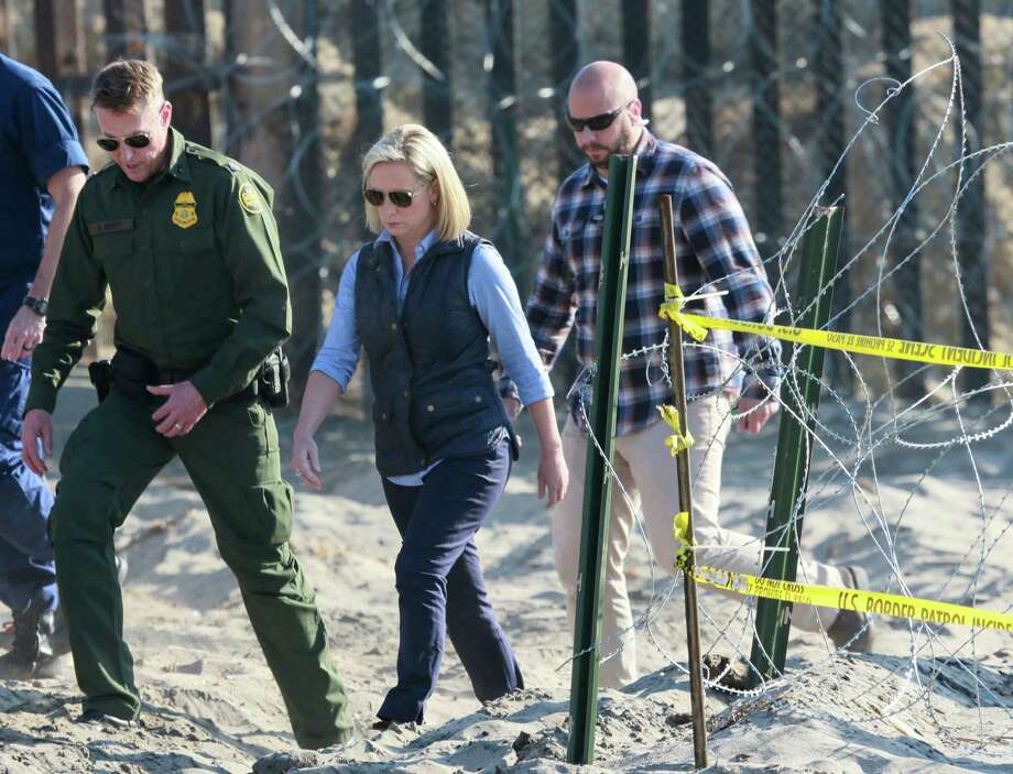 """Remember the """"beautiful"""" border wall that Mexico would pay for? Kirstjen M. Nielsen, center, Secretary of the Department of Homeland Security recently visited the border and said mission accomplished with more wire and fence. Photo: SANDY HUFFAKER /AFP /Getty Images / AFP or licensors"""
