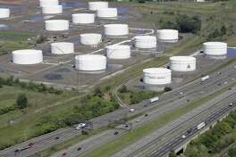 FILE - In this Sept. 8, 2008 file photo, traffic on I-95 passes Citgo oil storage tanks in Linden, N.J. Venezuela will hold onto its U.S.-based Citgo refineries, settling in Nov. 2018 a dispute that threw ownership of the struggling country?'s prized assets into peril. (AP Photo/Mark Lennihan, File)