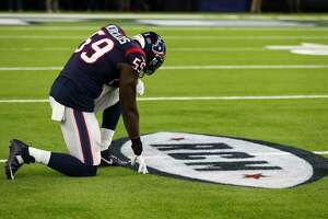 Houston Texans outside linebacker Whitney Mercilus (59) kneels down in front of a painted tribute to deceased Texans owner Bob McNair before the first quarter of an NFL football game at NRG Stadium on Monday, Nov. 26, 2018, in Houston.