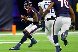 Houston Texans quarterback Deshaun Watson (4) evades Tennessee Titans outside linebacker Brian Orakpo (98) during the first quarter of an NFL football game at NRG Stadium on Monday, Nov. 26, 2018, in Houston.