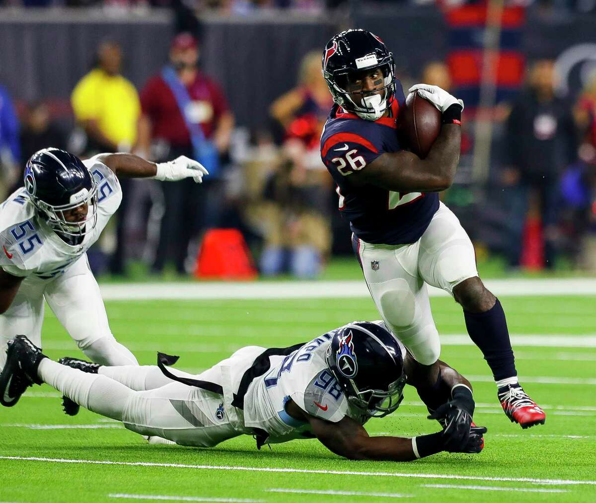 Houston Texans running back Lamar Miller (26) tries to escape Tennessee Titans outside linebacker Brian Orakpo (98) during the first quarter of an NFL football game at NRG Stadium on Monday, Nov. 26, 2018, in Houston.