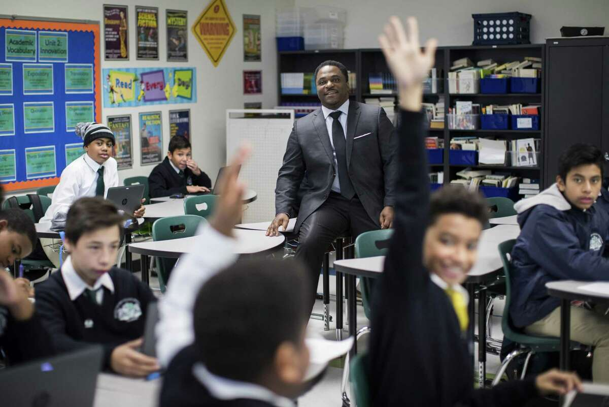 Mickey Leland College Preparatory Academy for Young Men Principal Dameion Crook interact with seventh graders working on an assignment about creating original ideas during class, Thursday, Nov. 15, 2018, in Houston.