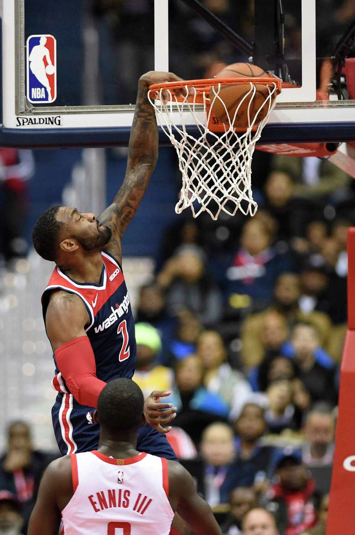 Washington Wizards guard John Wall (2) dunks against Houston Rockets forward James Ennis III (8) during the first half of an NBA basketball game, Monday, Nov. 26, 2018, in Washington. (AP Photo/Nick Wass)