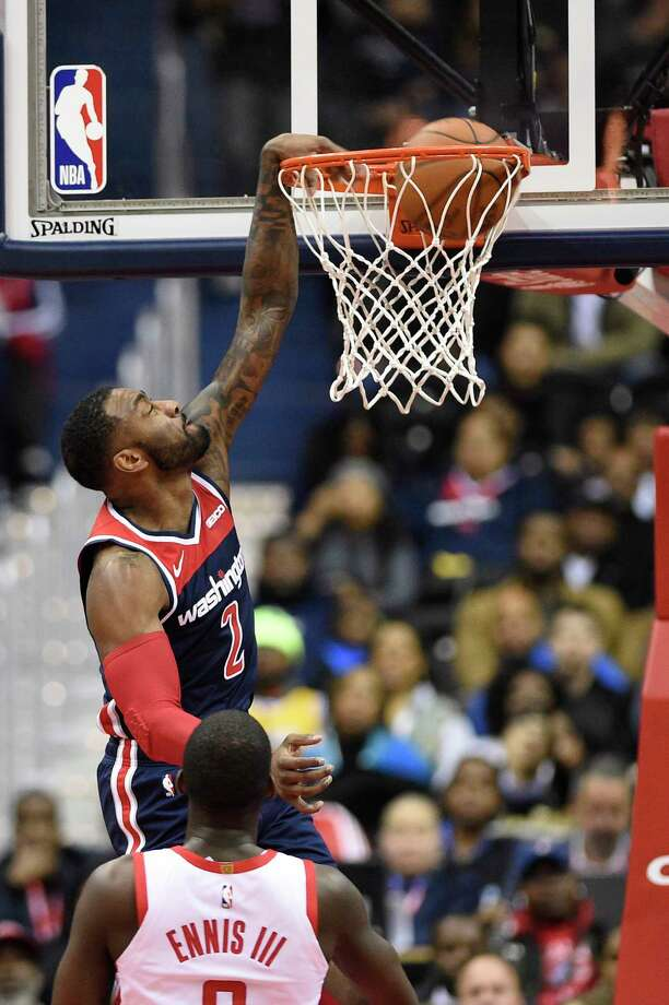 Washington Wizards guard John Wall (2) dunks against Houston Rockets forward James Ennis III (8) during the first half of an NBA basketball game, Monday, Nov. 26, 2018, in Washington. (AP Photo/Nick Wass) Photo: Nick Wass, Associated Press / Copyright 2018 The Associated Press. All rights reserved.