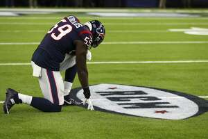 Houston Texans outside linebacker Whitney Mercilus kneels in front of a painted tribute to Texans owner Bob McNair on Nov. 26 at NRG Stadium. McNair, 81, died Nov. 23.